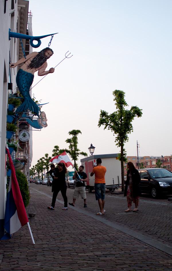 De Libanese en Nederlandse vlag worden naar binnen gehaald bij Libanees restaurant 'De Parel' in Historisch Delfshaven.