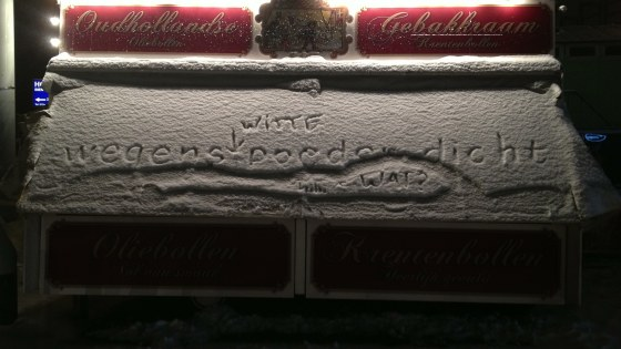 Besneeuwde oliebollenkraam. iemand heeft 'wegens witte poeder dicht' in de sneeur geschreven